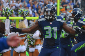Kam Chancellor high fives teammates after coming out of the tunnel at CenturyLlink.
